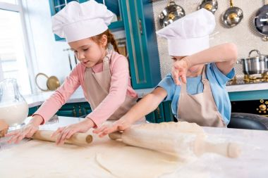 focused little children in chef hats and aprons rolling dough in kitchen
