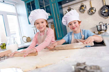 children preparing dough and smiling at camera in kitchen