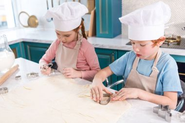 adorable little children in chef hats and aprons preparing cookies together