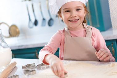 adorable child in chef hat and apron smiling at camera while preparing cookies
