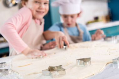 close-up view of uncooked dough and forms for cookies and cute little children in kitchen