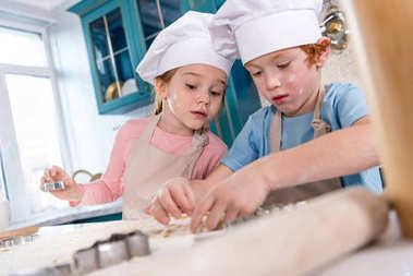 cute little children in chef hats and aprons preparing cookies together
