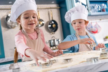adorable little kids in chef hats and aprons preparing cookies together