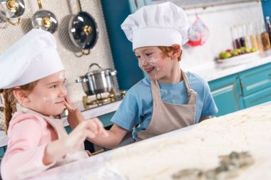 cute little kids in chef hats having fun with flour in kitchen