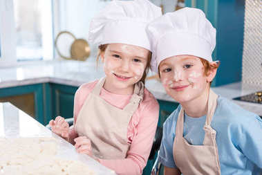 cute little children in chef hats and flour on faces smiling at camera