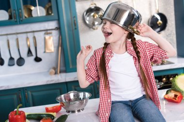 happy little child with pan on head sitting on kitchen table