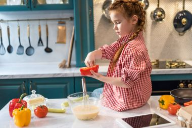 adorable little child cooking while sitting on kitchen table