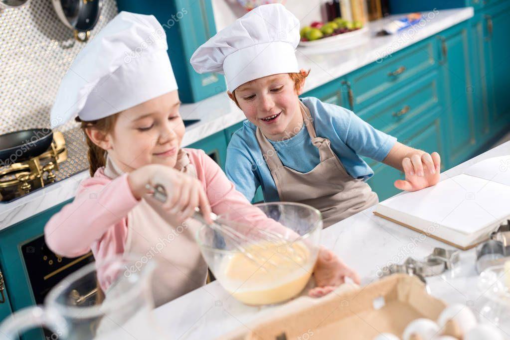 happy children in chef hats making dough in kitchen