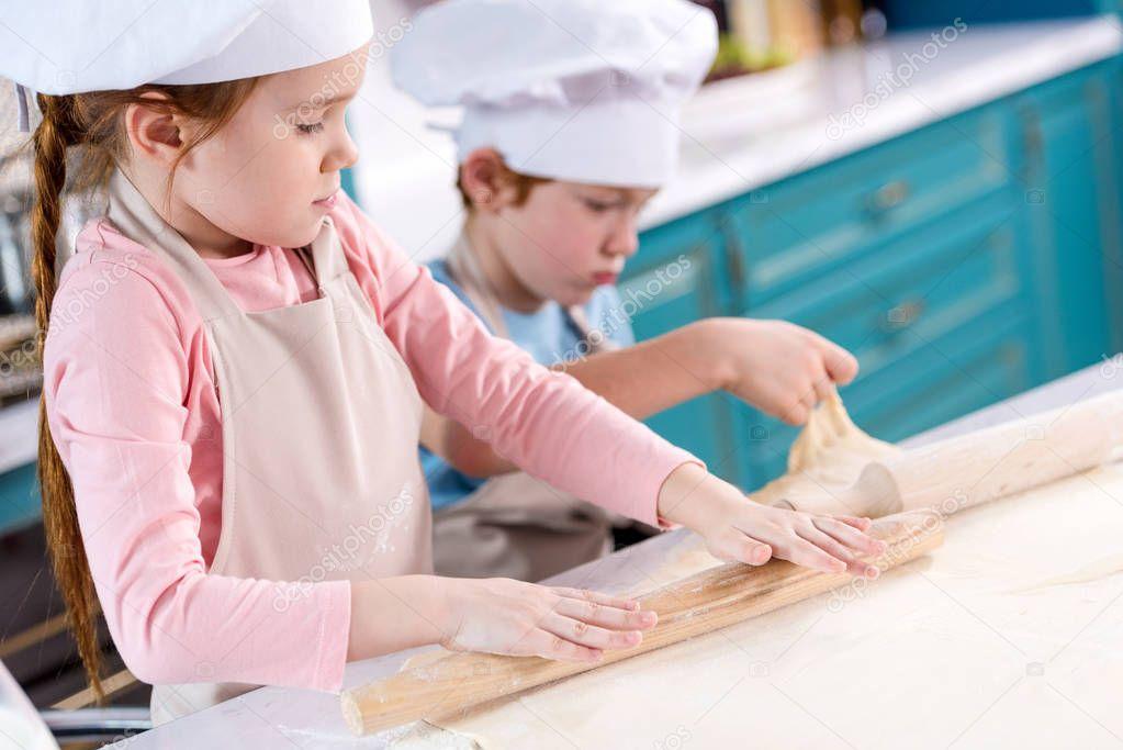 children preparing dough for cookies in kitchen