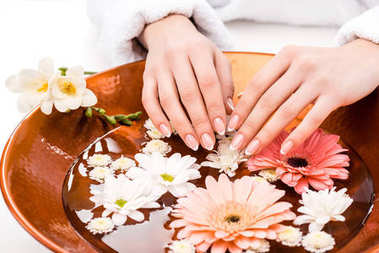 cropped view of woman making spa procedure with flowers in beauty salon, nail care concept