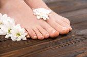 oříznutý pohled nohou s přírodní pedikúra a květiny na dřevěný povrch