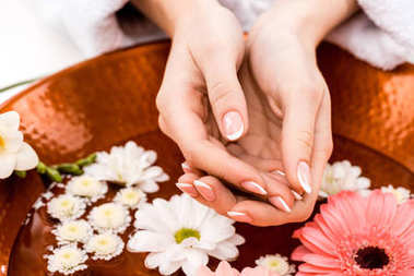 cropped view of woman making spa procedure with flowers in beauty salon