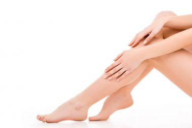 cropped view of beautiful female legs and hands, isolated on white
