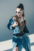 modello alla moda che propone in occhiali da sole e stile denim
