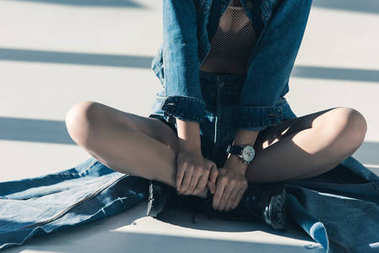cropped view of woman in denim clothes sitting on floor with shadows