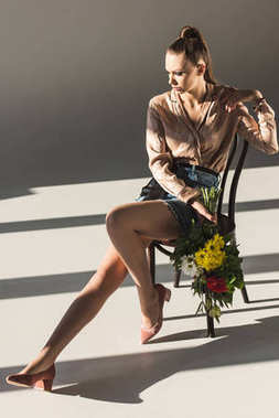 beautiful fashionable girl with bouquet of flowers posing on chair