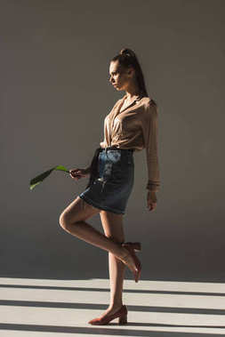 fashionable young woman in denim skirt and blouse holding green leaf