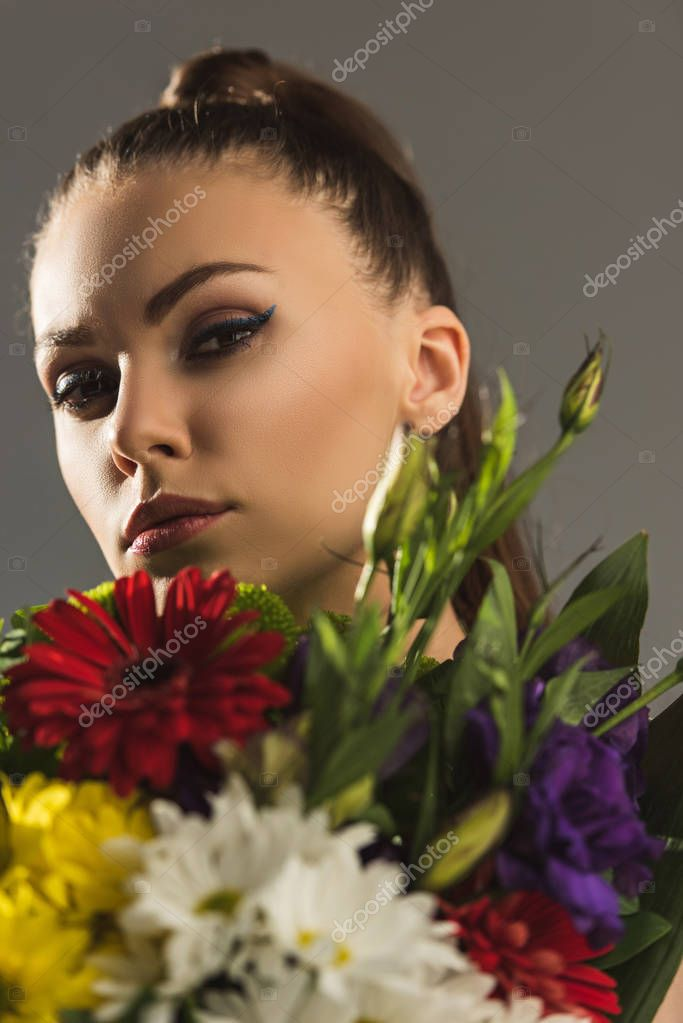 portrait of beautiful girl with bouquet of flowers looking at camera, isolated on grey