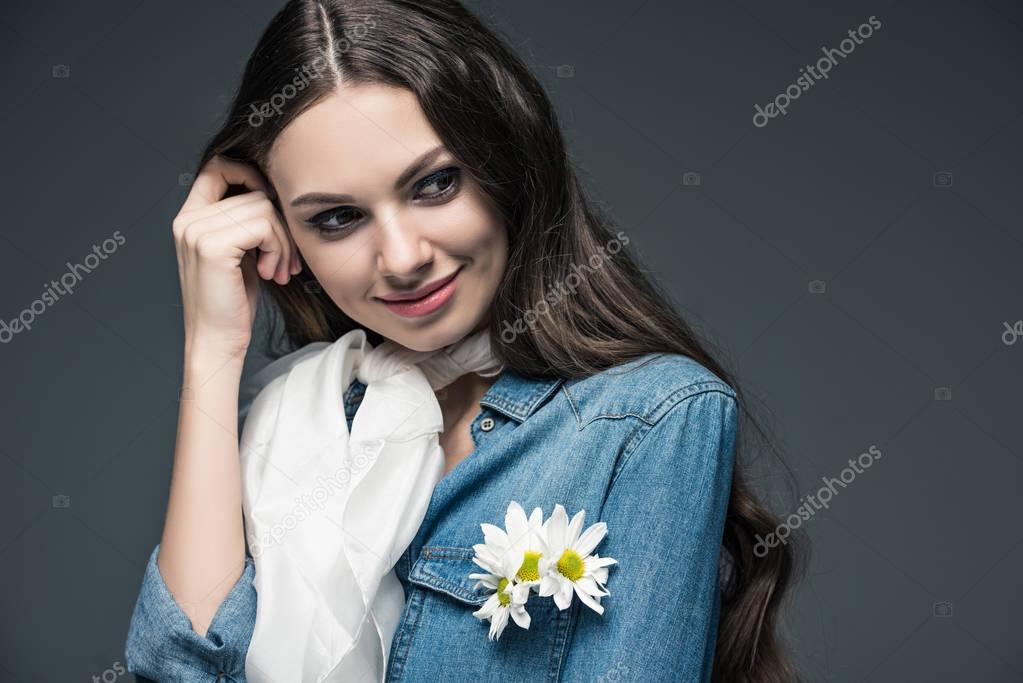 smiling girl posing in scarf and denim shirt with flowers, isolated on grey