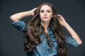 attraktives Mädchen mit langen Haaren posiert im Jeanshemd, isoliert auf grau
