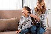matka, kartáčování vlasy rozkošný usměvavá malá dcerka doma