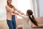 krásná šťastná matka a dcera, drželi se za ruce a usmívá se navzájem doma
