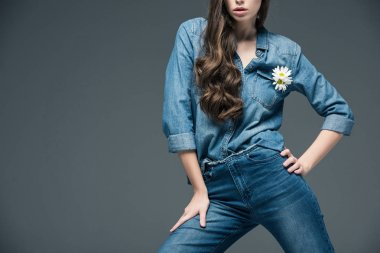 cropped view of girl posing in denim shirt with flower, isolated on grey