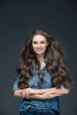 beautiful cheerful girl with long hair posing in denim shirt, isolated on grey