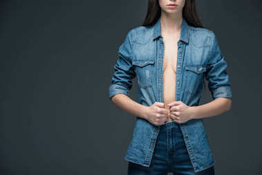 cropped view of woman posing in trendy denim clothes, isolated on grey