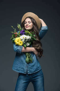 attractive smiling girl with closed eyes in denim clothes and straw hat holding bouquet of flowers, isolated on grey