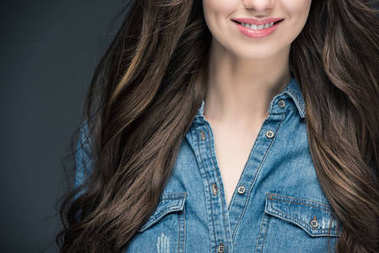 cropped view of smiling brunette girl with long hair, isolated on grey