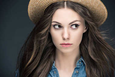 portrait of attractive girl with long hair in straw hat, isolated on grey