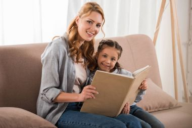 happy mother and daughter reading book and smiling at camera together at home