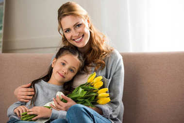 happy mother and daughter with yellow tulips sitting together and smiling at camera