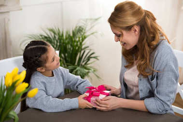 adorable child presenting gift box to mother at home