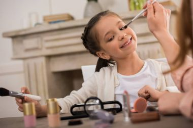 cropped shot of mother applying makeup to adorable happy little daughter