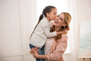 cute little child kissing happy mother at home
