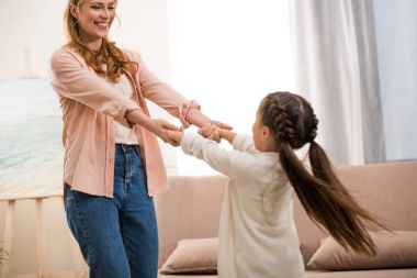 beautiful happy mother and daughter holding hands and smiling each other at home