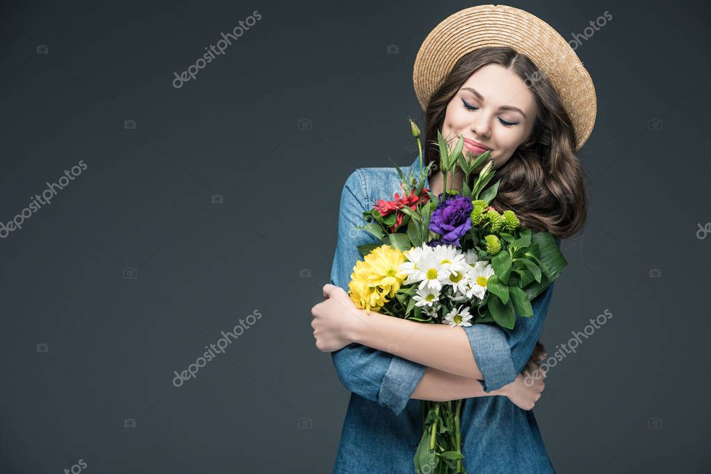 beautiful happy woman with closed eyes holding flowers for 8 march, isolated on grey