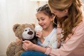 krásná šťastná matka a dcera hraje s plyšovým medvědem doma