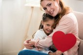 Fotografie happy mother and daughter with red heart symbol hugging and smiling at camera