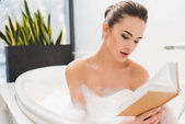 Fotografie portrét mladé ženy čtení knihy při přijetí koupele
