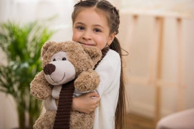 adorable little child hugging teddy bear and smiling at camera