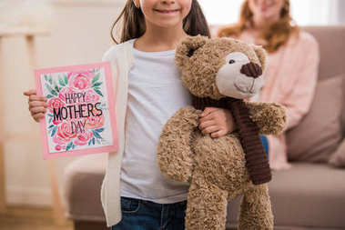 cropped shot of happy child holding teddy bear and happy mothers day greeting card