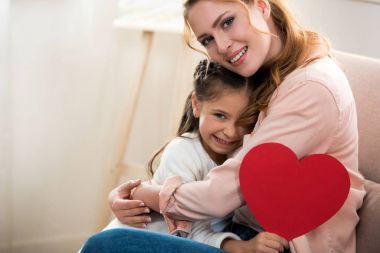 happy mother and daughter with red heart symbol hugging and smiling at camera