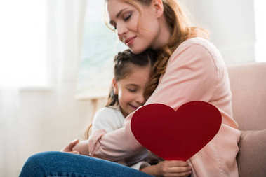 happy mother and daughter with red heart symbol hugging at home