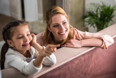 happy mother and daughter pointing with finger and looking away