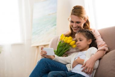 happy mother and daughter with yellow tulips using smartphone together at home