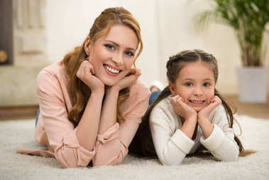 beautiful happy mother and daughter lying on carpet and smiling at camera