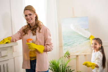 beautiful happy mother and daughter cleaning room and smiling at camera